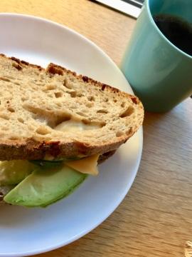Smörgås med avokad och ost på vitt fat, till höger en grön kaffekopp med svart kaffe i