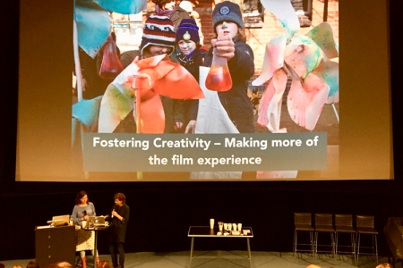Two women at a stage, image with children in the background and the text Fostering Creativity - making mor of the film experience