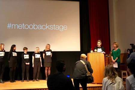 Kvinnor på rad på en scen, en talstol till höger där två ytterligare kvinnor står