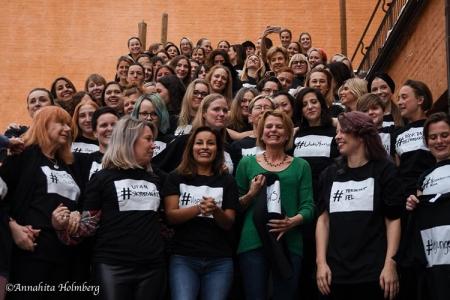 Massor av kvinnor i en trappa, alla med svarta tröjor med vid ruta på bröstet. I rutan en # och handskriven text