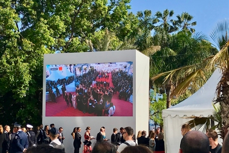 Big screen showing red carpet with people gathered on it